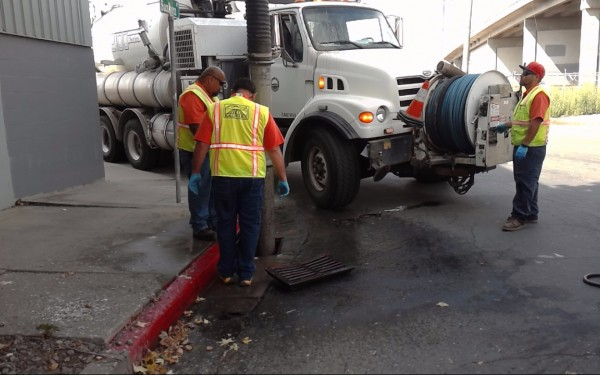 City Workers Pumping sewage from storm drain